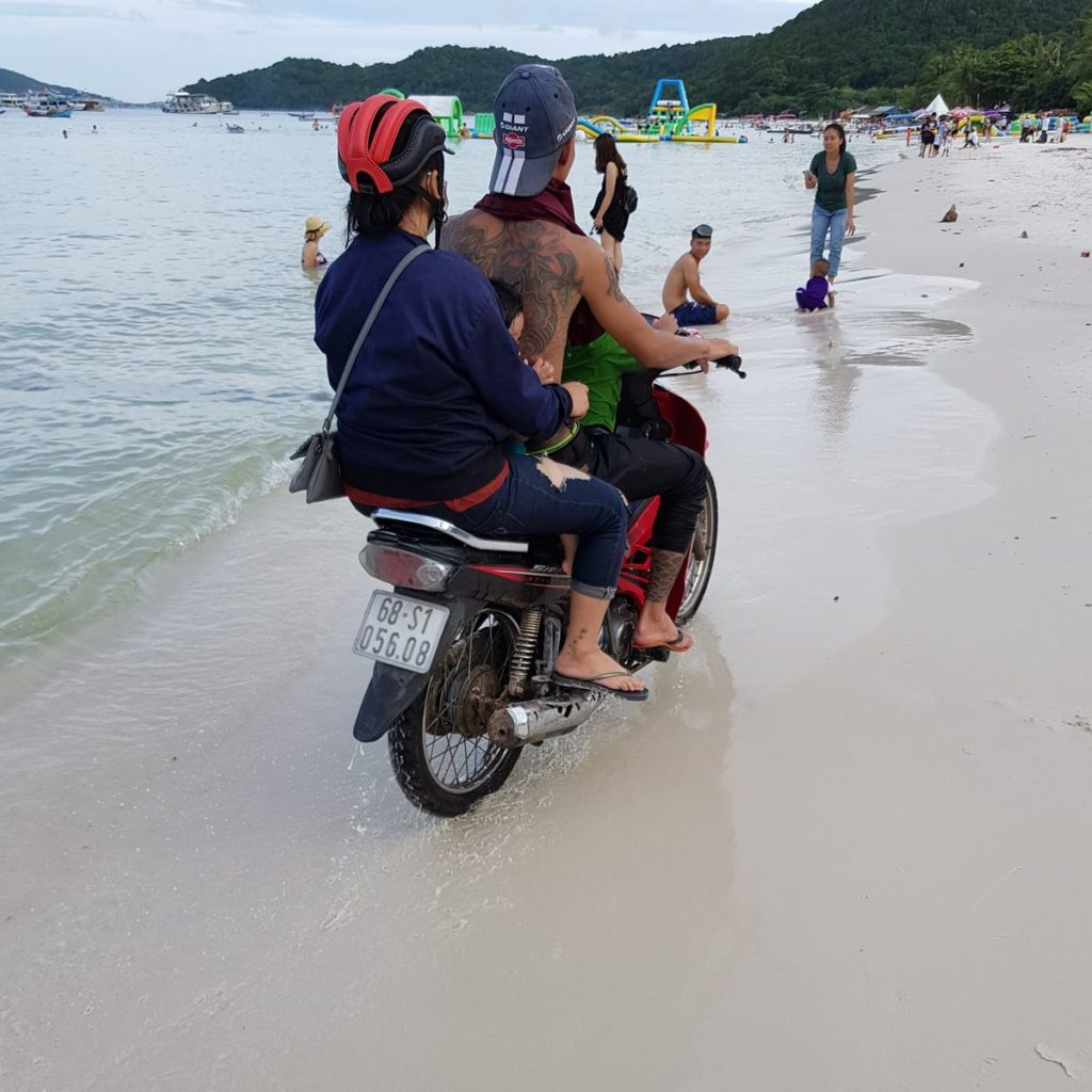 мотоциклист едет по пляжу